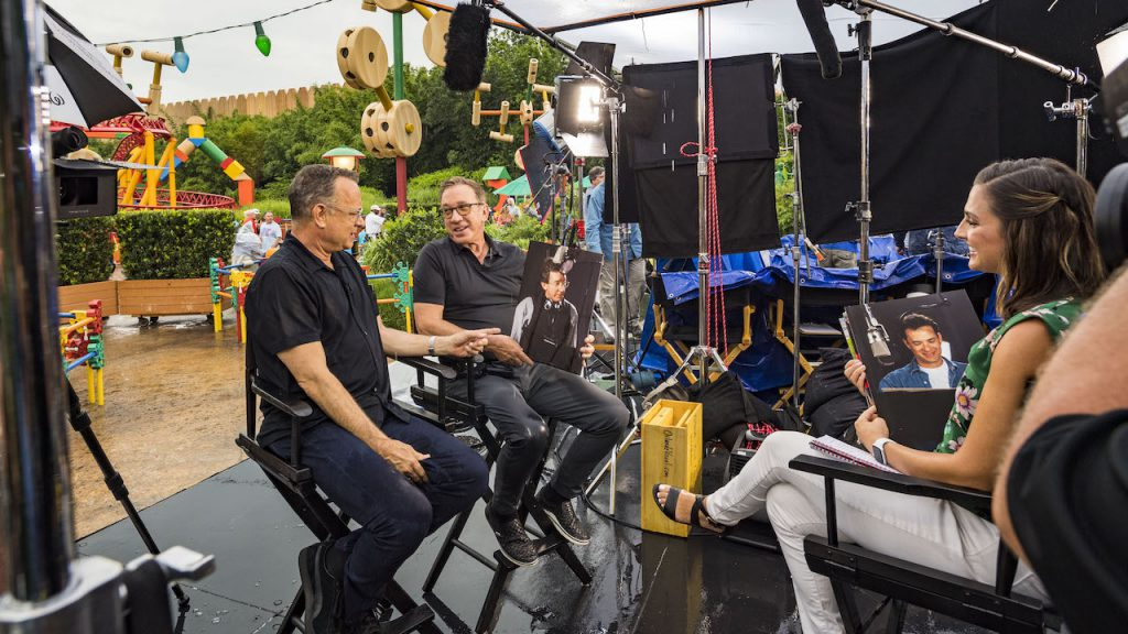 "Tom Hanks (left) and Tim Allen (center), stars of Disney and Pixar's ""Toy Story 4,"" with Paula Faris from GMA (right) inside Toy Story Land at Disney's Hollywood Studios"