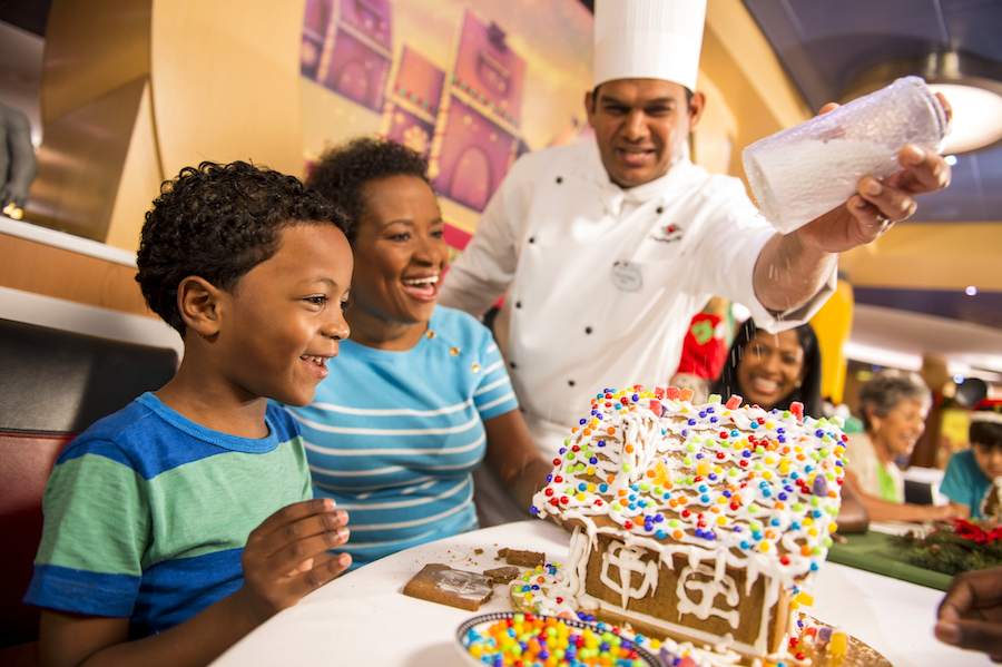 Family decorating a gingerbread house on Disney Cruise Line