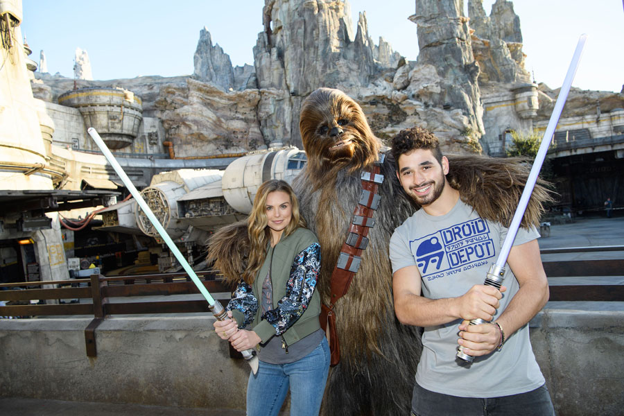 """Dancing with the stars"" contestant ""The Bachelorette"" Hannah Brown, and her partner, professional dancer Alan Bersten, pose with Chewbacca in Star Wars: Galaxy's Edge"