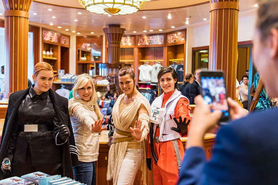 Guests dressed in Star Wars costumes pose with Ashley Eckstein