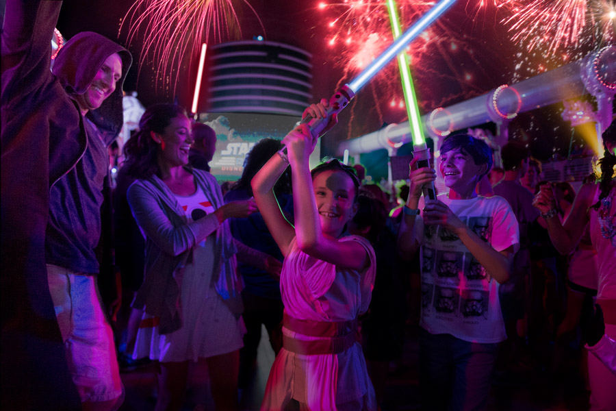 """Little girl dresses as Rey and her family at the """"Summon the Force"""" deck party during Star Wars Day at Sea"""